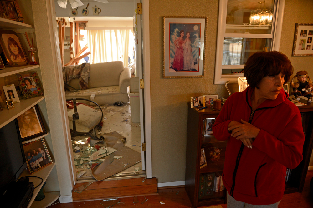 . Gloria Solis has a hard time looking at the damage to her home after an SUV crashed into the house, at the 5100 block of Gill Place in Denver, April 04, 2013. No one inside the home was hurt. (Photo By RJ Sangosti/The Denver Post)