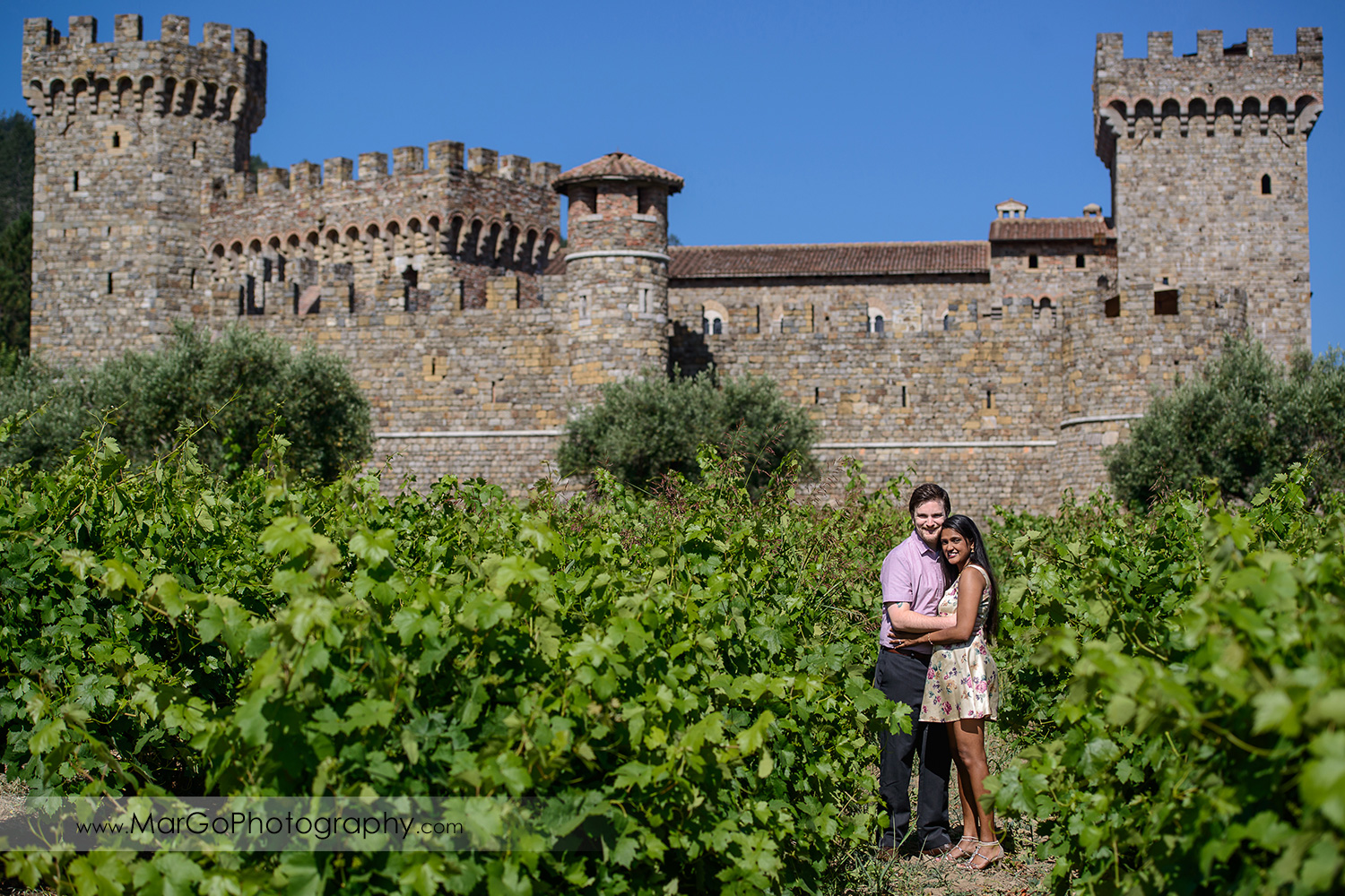 man in pink shirt and Indian woman in flower dress hugging in the vineyard in front of the castle during engagement session at Castello di Amorosa in Calistoga