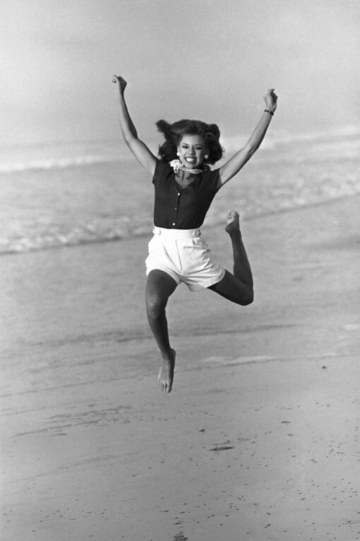 . Vanessa Williams, Miss America for 1984, jumps for photographers on the beach in Atlantic City, New Jersey, Sept. 19, 1983. She is the first black Miss America in the pageant\'s history. (AP Photo)