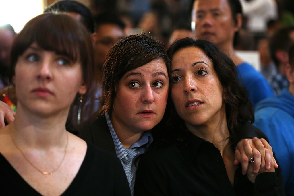 . Same-sex couple Lori Bilella, center, and Renara Moreira, right, await results from the U.S. Supreme Court\'s rulings on gay marriage in City Hall June 26, 2013, in San Francisco, Calif. The high court struck down the Defense of Marriage Act (DOMA) and ruled that supporters of California\'s ban on gay marriage, Proposition 8, could not defend it before the Supreme Court. (Justin Sullivan/Getty Images)