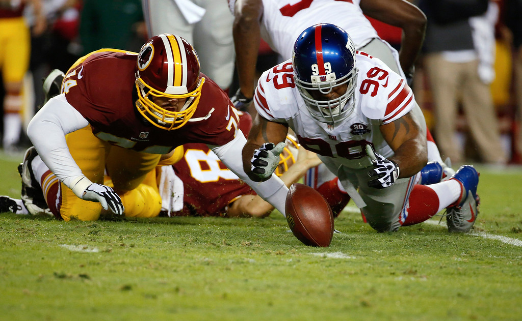 . New York Giants defensive tackle Cullen Jenkins (99) falls on a loose ball as Washington Redskins tackle Tyler Polumbus (74) closes in after Redskins quarterback Kirk Cousins was sacked during the first half of an NFL football game in Landover, Md., Thursday, Sept. 25, 2014. The New York Giants recoved the fumble. (AP Photo/Alex Brandon)