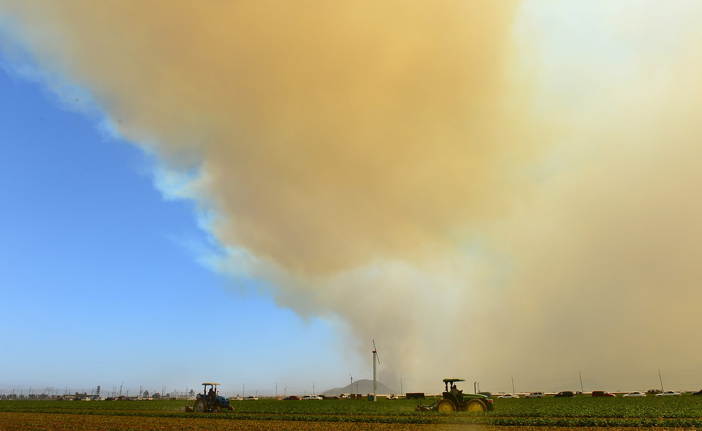 . Farmers drive their tractors on farmland off the Pacific Coast Highway south of Oxnard as smoke rising into the sky and fanned by strong winds ravage hillsides and canyons in nearby Ventura County, northwest of Los Angeles on May 2, 2013. An eight-mile (13-mile) section of the Pacific Coast Highway (PCH) was closed from about 10 miles west of Malibu due the Camarillo Springs fire, the California Highway Patrol reported. AFP PHOTO/Frederic J.  BROWN/AFP/Getty Images