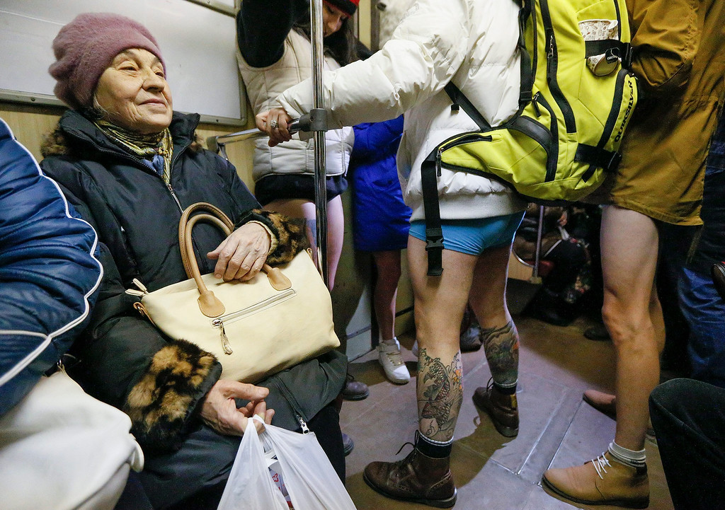 . An elderly woman looks on young Ukrainians wearing no pants as they participate in the first \'No Pants Subway Ride\' in Kiev, Ukraine, 12 January 2014. No Pants Subway Ride is an annual global event started in New York, USA in 2002. This is the first time that the event is organized in Ukraine.  EPA/SERGEY DOLZHENKO