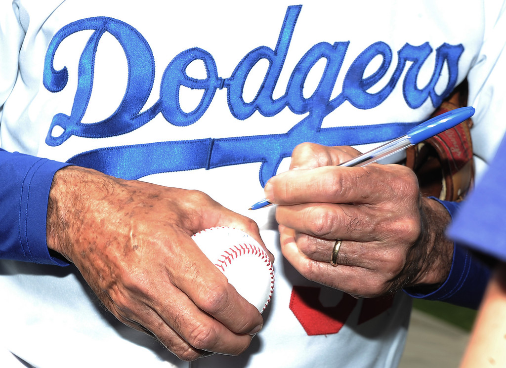 . Former Los Angeles and Brooklyn Dodger left handed pitcher Sandy Koufax signs Atlanta Braves\' Craig Kimbrel (not pictured) baseball during the Old-Timers game prior to a baseball game between the Atlanta Braves and the Los Angeles Dodgers on Saturday, June 8, 2013 in Los Angeles. 