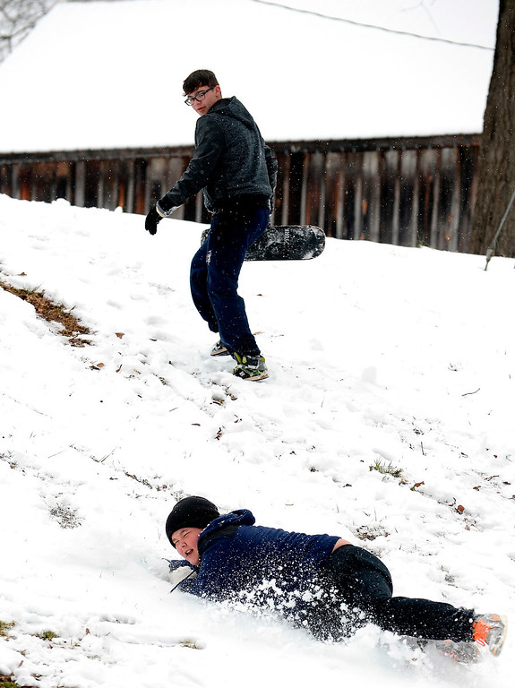 """. Micah Hulit, center, falls down in the snow as he and Aaron Warren slide down a hill in a winter snow storm that the National Weather Service predicted to be \""""an event of historical proportions\"""" blows into Georgia\'s Bartow County in Euharlee, Ga., about 40 miles north of metro Atlanta, on Tuesday, Feb. 11, 2014. (AP Photo/David Tulis)"""