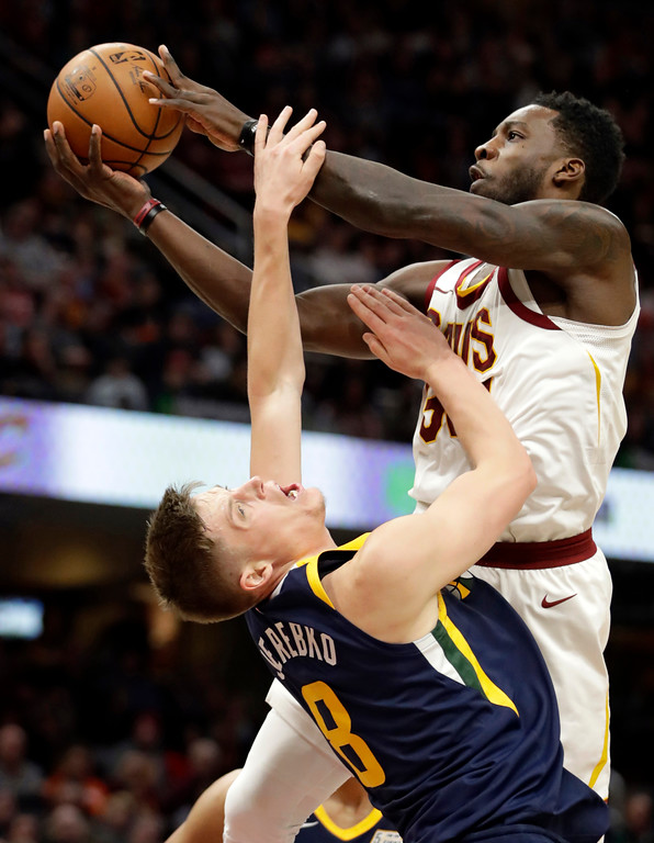 . Cleveland Cavaliers\' Jeff Green, top, fouls Utah Jazz\'s Jonas Jerebko (8), from Sweden, in the second half of an NBA basketball game, Saturday, Dec. 16, 2017, in Cleveland. (AP Photo/Tony Dejak)