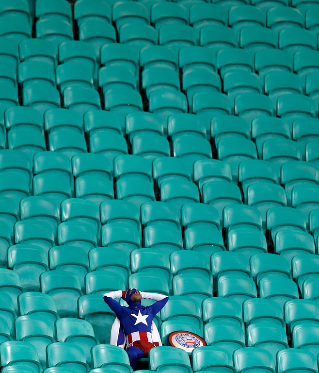 . A lone USA supporter dressed as \'Captain America\' sits in the stands after Belgium defeated the USA 2-1 in extra time to advance to the quarterfinals during the World Cup round of 16 soccer match between Belgium and the USA at the Arena Fonte Nova in Salvador, Brazil, Tuesday, July 1, 2014. (AP Photo/Natacha Pisarenko)