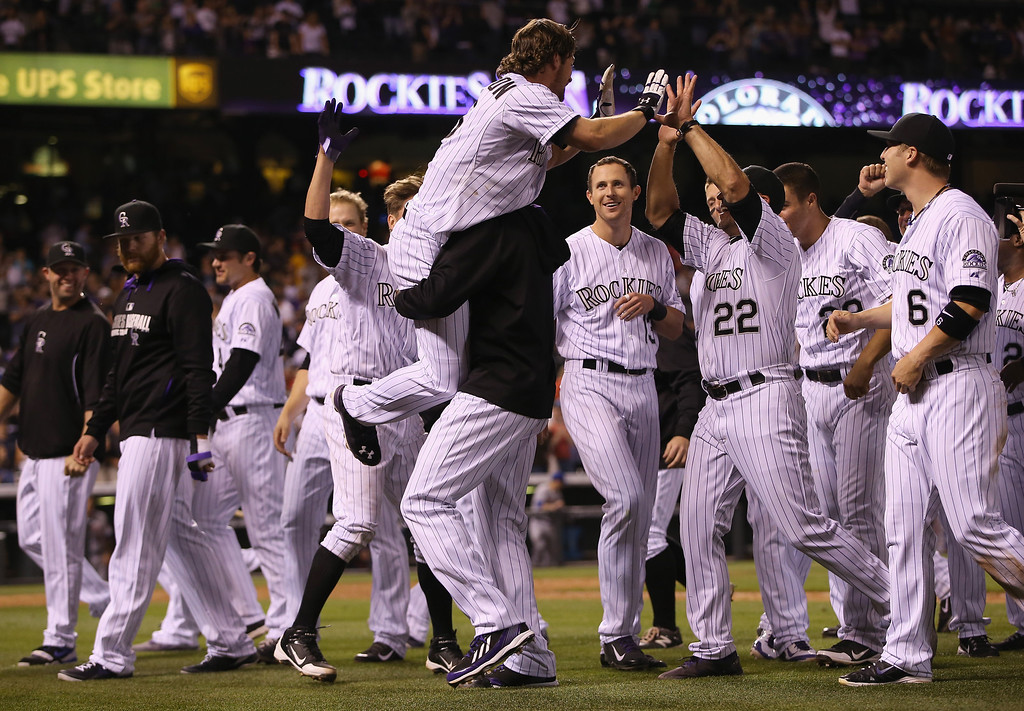 . DENVER, CO - MAY 03:  Charlie Culberson #23 of the Colorado Rockies is hoisted in the air by winning pitcher LaTroy Hawkins #32 of the Colorado Rockies as manager Walt Weiss #22 and the Colorado Rockies celebrate Culberson\'s game winning walk off two run pinch hit home run off of Kyle Farnsworth #44 of the New York Mets at Coors Field on May 3, 2014 in Denver, Colorado. The Rockies defeated the Mets 11-10.  (Photo by Doug Pensinger/Getty Images)