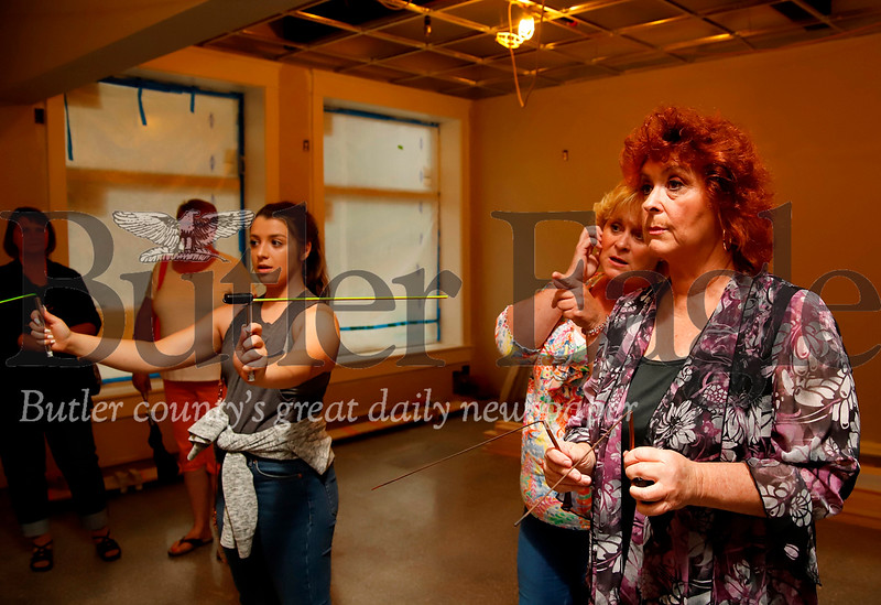 Suzanne Vincent(right) of Psychic Vincent Sisters Ghost Tours, attempts to channel spirits with her copper dowsing rods along with Evans City native Chelsea Mars. Mars' great grandmother(still living) used to work at the Kaufman House. Seb Foltz/Butler Eagle