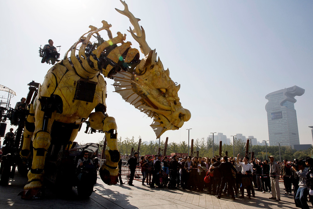 """. Tourists gather near the French production company La Machine\'s latest creation \""""the Long Ma\"""" or Dragon Horse during it\'s first show held in front of the Bird\'s Nest Stadium in Beijing, China, Friday, Oct. 17, 2014. A series of performances over three days will mark the climax of celebrations for the 50th anniversary of Sino-French diplomatic relations on Sunday, Oct 19.  (AP Photo/Ng Han Guan)"""