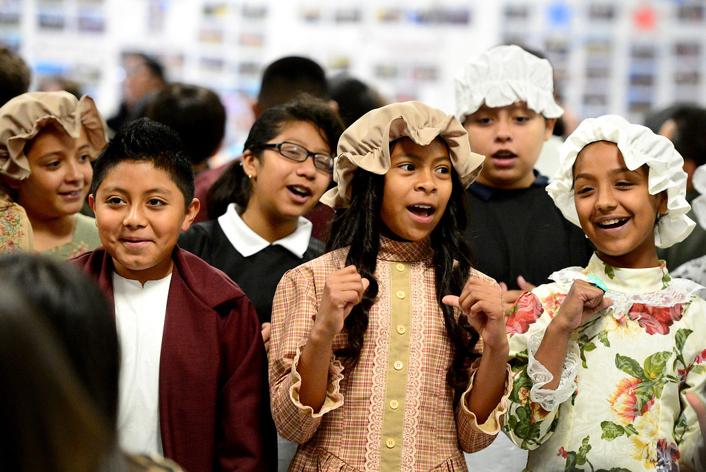 . From left, Edwin Martinez, Maricruz Becerra and Haley Almaraz sing an American folk song at Tracy Elementary School during a fifth-grade Colonial Festival Tuesday morning, March 26, 2013 at the Baldwin Park school. In one month the students completed a report, learned two songs and two dances. Grecia Herrera, the school\'s nutritional aid, made the dresses and boys\' suits. (SGVN/Staff Photo by Sarah Reingewirtz)