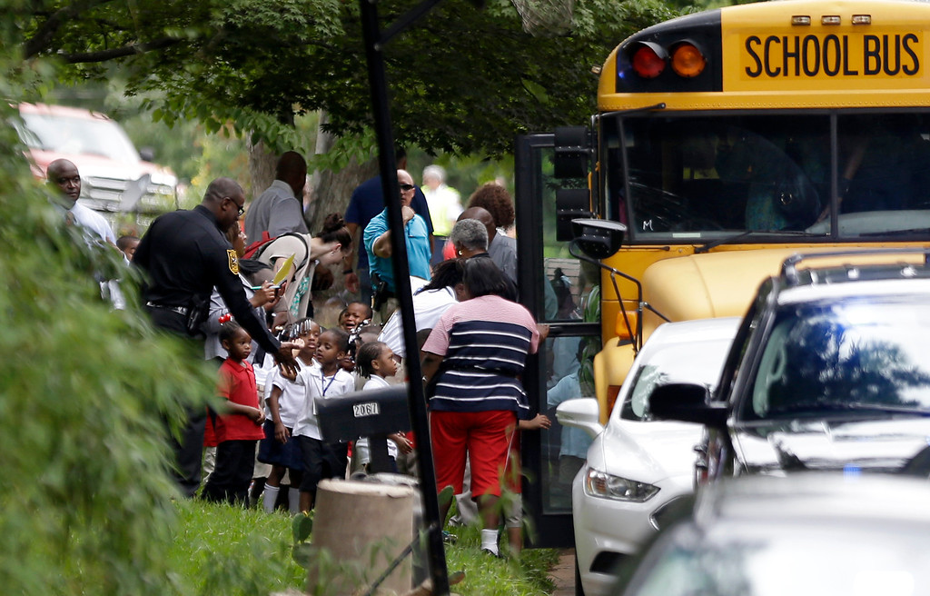 . A police officer gives a high-five to students from Ronald E. McNair Discovery Learning Academy as they board school buses to take them to reunite with their parents as they were evacuated after reports of a gunman entered the school, Tuesday, Aug. 20, 2013, in Decatur, Ga. All students and teachers are safe and a suspect is in custody after gunfire was heard at the Atlanta-area elementary school today. (AP Photo/David Goldman)