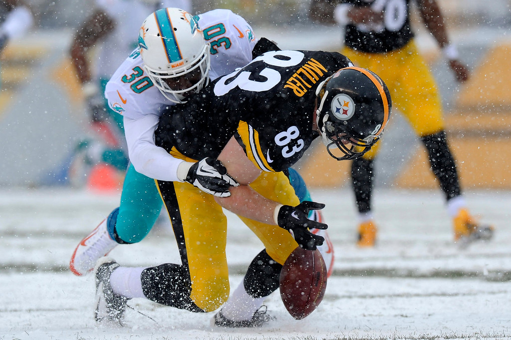 . Pittsburgh Steelers tight end Heath Miller (83) fumbles as he is tackled by Miami Dolphins strong safety Chris Clemons (30) during the first half of an NFL football game in Pittsburgh, Sunday, Dec. 8, 2013. Miller recovered the fumble. (AP Photo/Don Wright)