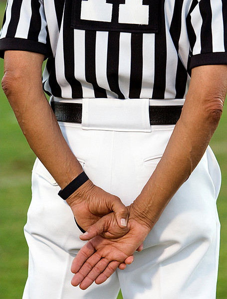 the hands of a football head linesman, waiting to make a call