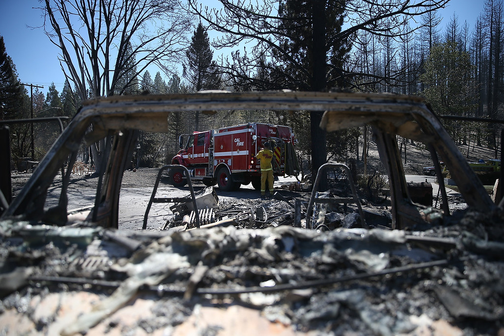 . Firefighters stand by in front of the remains of a destroyed home on September 16, 2014 in Weed, California. A fast moving wildfire fueled by high winds ripped through the town of Weed on the afternoon of September 15, burning 100 structures including the high school and lumber mill.  (Photo by Justin Sullivan/Getty Images)