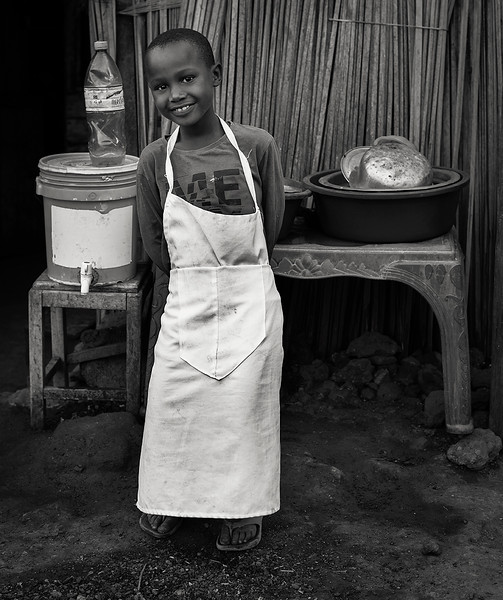 Young boy working in a street food stall.  Mto wa Mbu village, Tanzania, 2019
