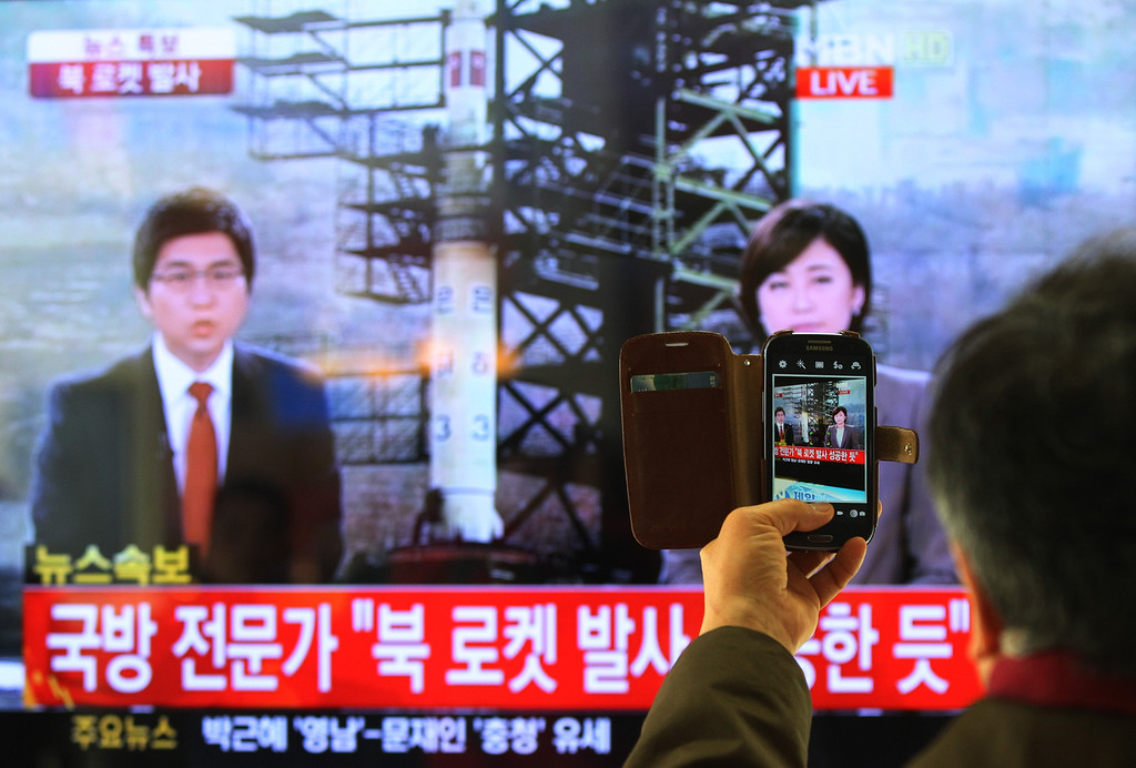 ". South Korean man uses his smartphone to take a television screen reporting a news about North Korea\'s rocket launch at Seoul Railway Station in Seoul, South Korea, Wednesday, Dec. 12, 2012. North Korea fired a long-range rocket Wednesday in its second launch under its new leader, South Korean officials said, defying warnings from the U.N. and Washington only days before South Korean presidential elections. The letters on the screen read "" North Korea\'s rocket launch seems to be successful.\"" (AP Photo/Ahn Young-joon)"