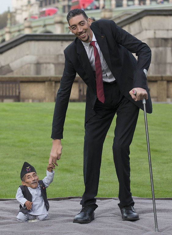 . Chandra Bahadur Dangi, from Nepal, (L) the shortest adult to have ever been verified by Guinness World Records, is pictured with the world\'s tallest man Sultan Kosen from Turkey, during a photocall in London on November 13, 2014, to mark Guinness World Records Day. Chandra Dangi, measures a tiny 21.5in (0.54m)  the same height as six stacked cans of beans. Sultan Kosen measures 8 ft 3in (2.51m).  AFP PHOTO / ANDREW COWIE/AFP/Getty Images