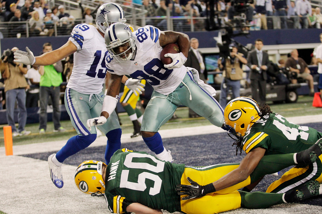 . Dallas Cowboys wide receiver Dez Bryant (88) pulls in a touchdown pass over Green Bay Packers inside linebacker A.J. Hawk (50) and free safety M.D. Jennings (43) as Cowboys\' wide receiver Miles Austin (19) looks on during the second half of an NFL football game, Sunday, Dec. 15, 2013, in Arlington, Texas. (AP Photo/Tim Sharp)
