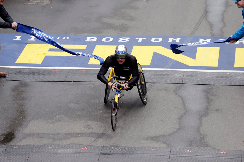 . Marcel Hug, of Switzerland, breaks the tape at  the finish line to win the wheelchair division of the Boston Marathon, Monday, April 20, 2015, in Boston. (AP Photo/Charles Krupa)
