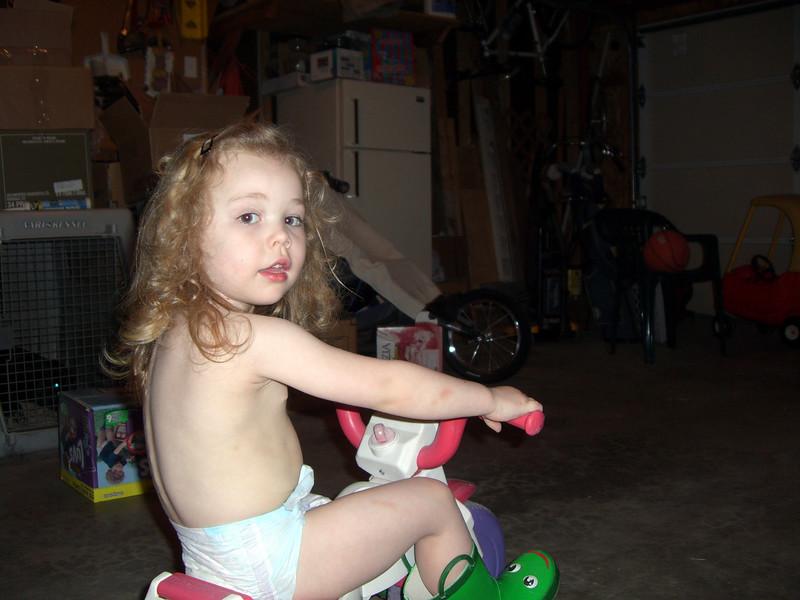 Riding her trike around the garage.