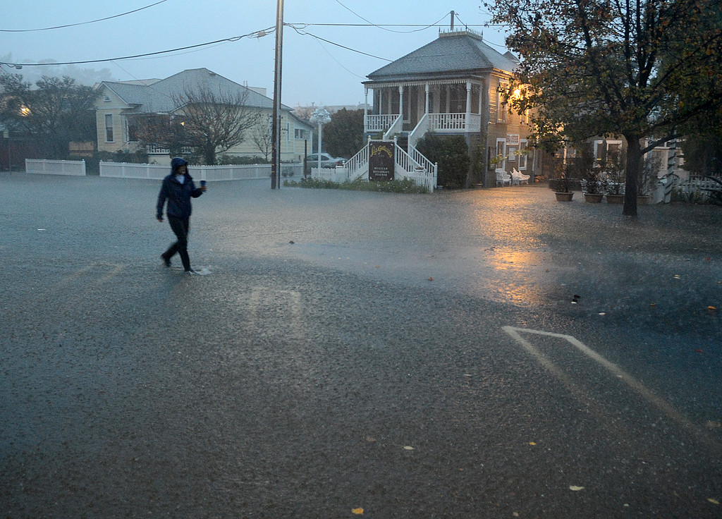 . With coffee in hand, Lisa Hutchinson walks through a downpour on Reichert Avenue in Novato, Calif., early in the morning on Thursday, Dec. 11, 2014. (Alan Dep/Marin Independent Journal)