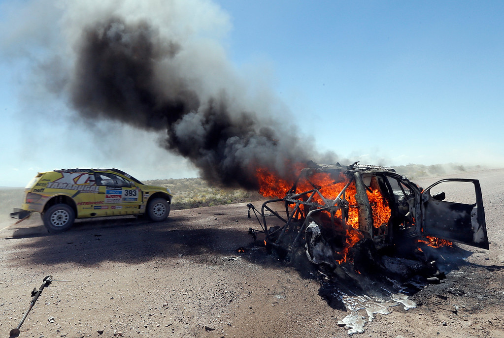 . The car of Javier Campillay of Chile and co-pilot Jose Ocampo of Argentina, left, drives by what remains of the Toyota of driver Bauyrzhan Issabayev and co-pilot Gabdulla Ashimov, both of Kazakhstan, during the second stage of the Dakar Rally between the cities of San Luis and San Rafael in San Rafael, Argentina,  Monday, Jan. 6, 2014. (AP Photo/Jean-Paul Pleissier, Pool)