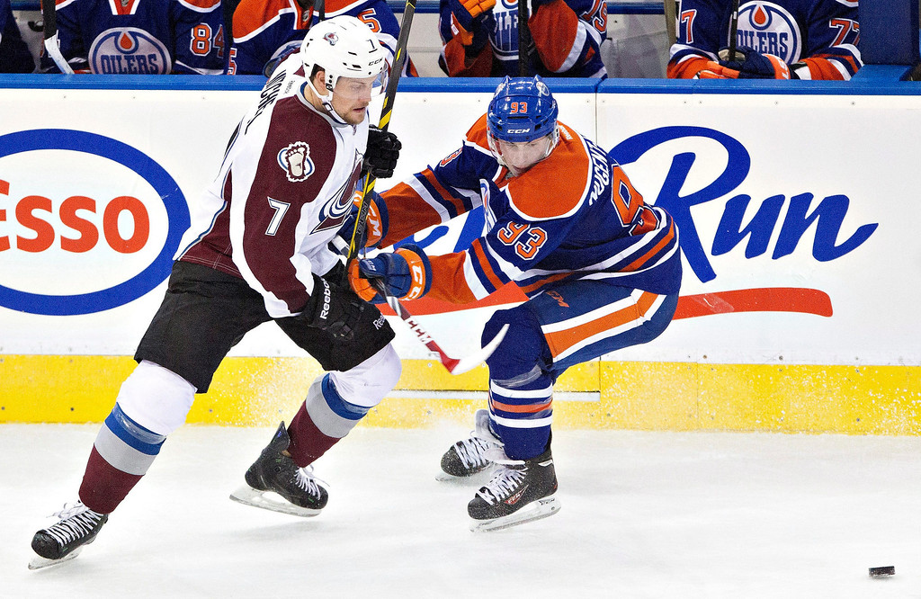. Colorado Avalanche\'s John Mitchell (7) is checked by Edmonton Oilers\' Ryan Nugent-Hopkins (93) during second period NHL hockey action in Edmonton, Alberta, on Tuesday April 8, 2014. (AP Photo/The Canadian Press, Jason Franson)