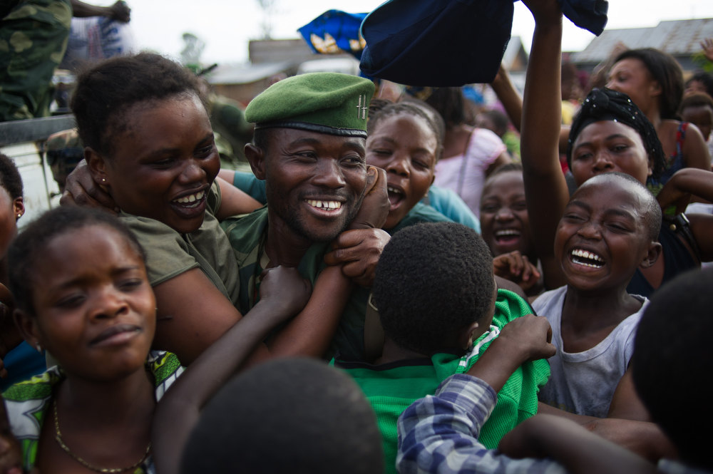 . Residents of the district around the military barracks celebrate as a Congolese government army (FARDC) soldier arrives back in Goma, eastern Democratic Republic of the Congo on December 3, 2012. Democratic Republic of Congo troops entered the eastern mining hub of Goma Monday, two days after rebel M23 fighters ended an almost fortnight-long occupation in line with a regionally brokered deal. The rebels are demanding that the Congolese government begin complex negotiations with them and have threatened to march back into Goma if Kinshasa reneges on a pledge they say was made to begin talks. PHIL MOORE/AFP/Getty Images
