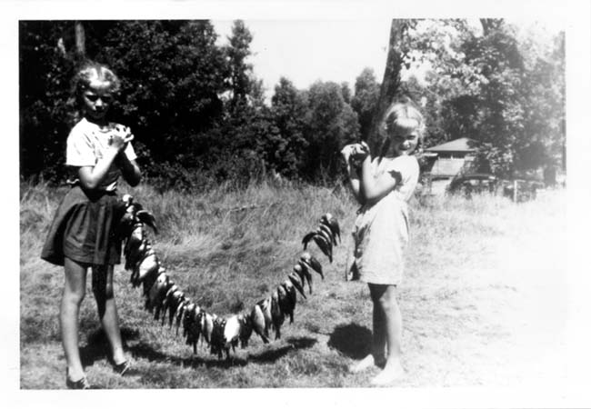 ". Reports MINNESOTA MAIDEN: ""With the fishing opener around the corner, I found this memorable photo of my sister, Jan, and myself, circa 1945. My aunt owned a resort on Big McDonald Lake, and the picture was taken during a family fishing trip. As you can see from our body language, this was some catch!\"""