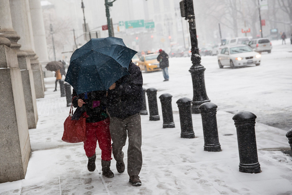 . A couple walks through a snow storm that is moving through the Northeast on January 21, 2014 in New York City.   (Photo by Andrew Burton/Getty Images)