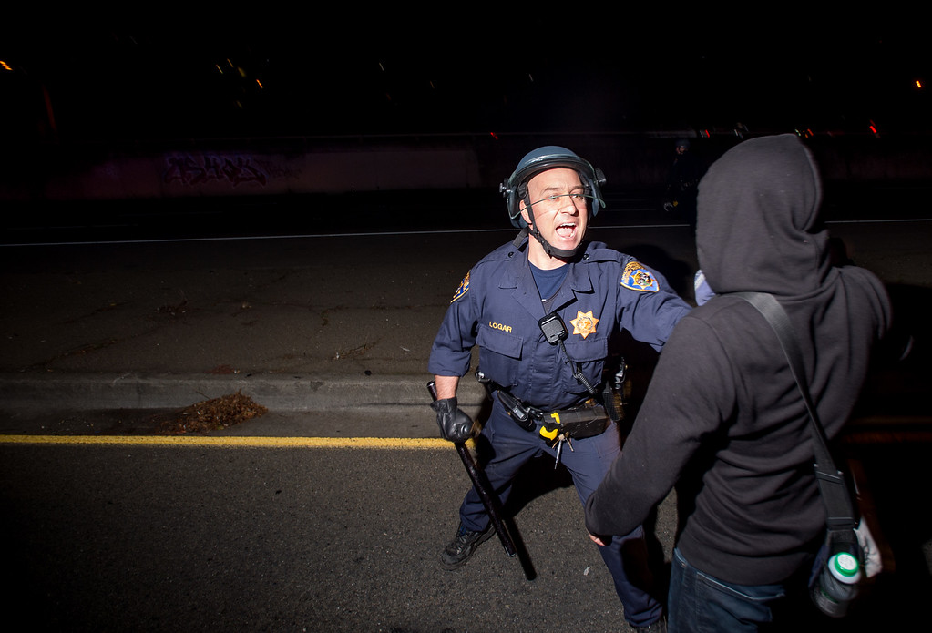. A police officer tries unsuccessfully to keep a protester from blocking Interstate 580 in Oakland, Calif on Monday, Nov. 24, 2014,  after the announcement of the grand jury decision not to indict Ferguson police officer Darren Wilson in the fatal shooting of Michael Brown, an unarmed 18-year-old. (AP Photo/Noah Berger)