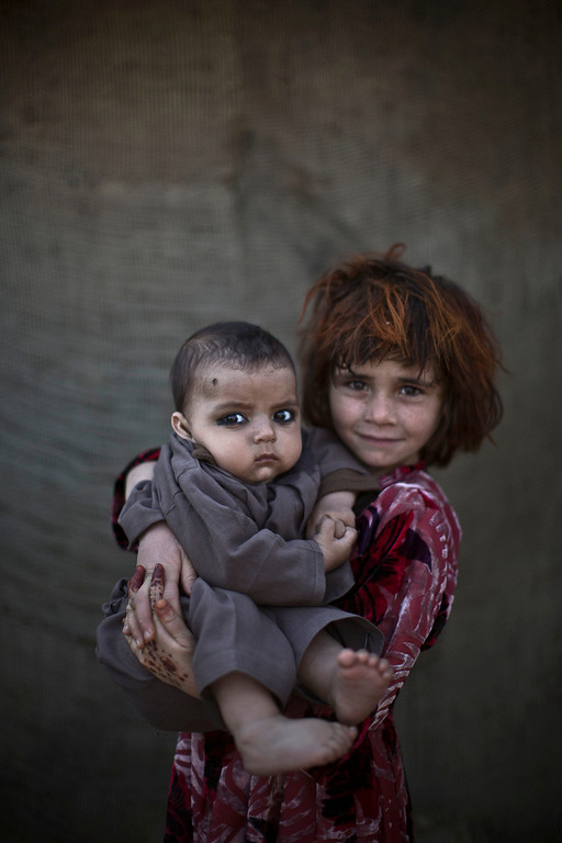 . In this Monday, Jan. 27, 2014 photo, Afghan refugee girl, Khalzarin Zirgul, 6, holds her cousin, Zaman, 3 months, as they pose for a picture, while playing with other children in a slum on the outskirts of Islamabad, Pakistan, Monday, Jan. 27, 2014. For more than three decades, Pakistan has been home to one of the world�s largest refugee communities: hundreds of thousands of Afghans who have fled the repeated wars and fighting their country has undergone. Since the 2002 U.S.-led invasion of Afghanistan, some 3.8 million Afghans have returned to their home country, according to the U.N.�s refugee agency. (AP Photo/Muhammed Muheisen)