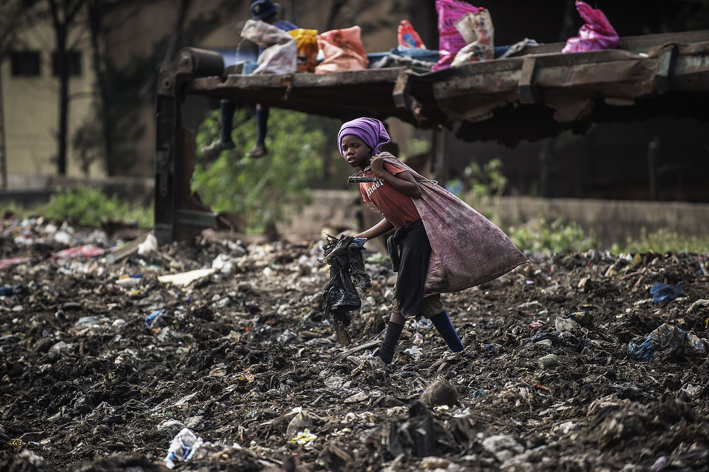 . A girl sifts through garbage at the Maputo municipal garbage dumping site in Maputo on October 14, 2014. GIANLUIGI GUERCIA/AFP/Getty Images