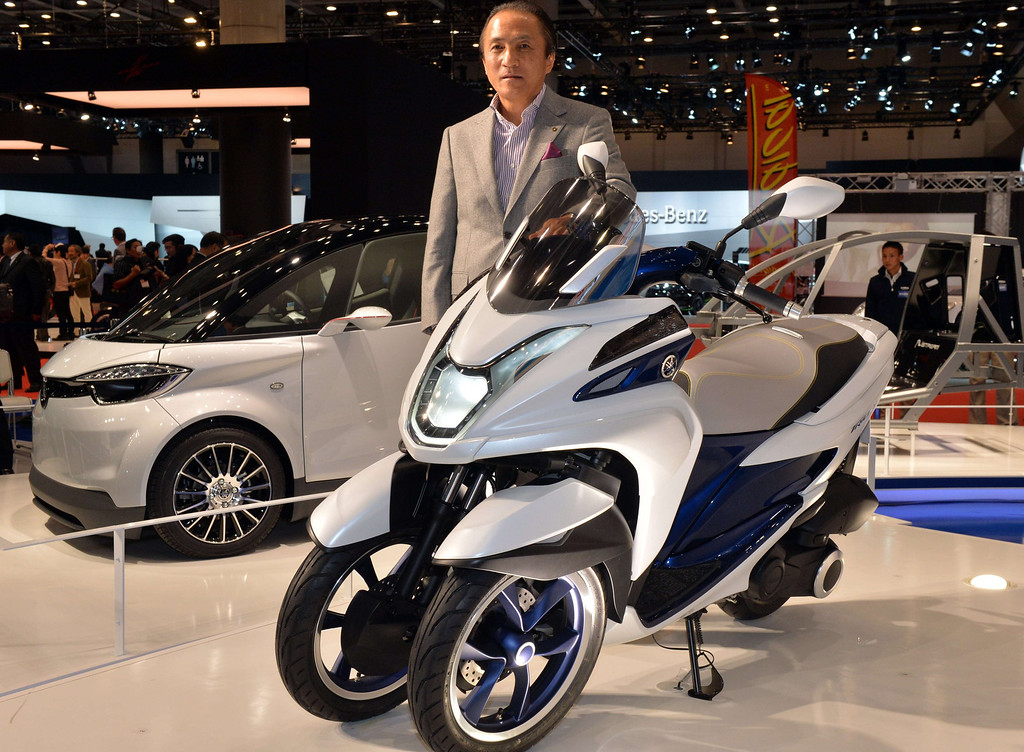 """. Japan\'s motorcycle giant Yamaha Motor president Hiroyuki Yanagi displays the prototype model of a trike \""""Tricity concept\"""" equipped with a 125cc engine with automatic transmission at the press preview of the Tokyo Motor Show in Tokyo on November 20, 2013. The  43rd Tokyo Motor Show  runs until December 1, features 177 exhibitors including parts suppliers from a dozen countries. .   AFP PHOTO / Yoshikazu TSUNO/AFP/Getty Images"""