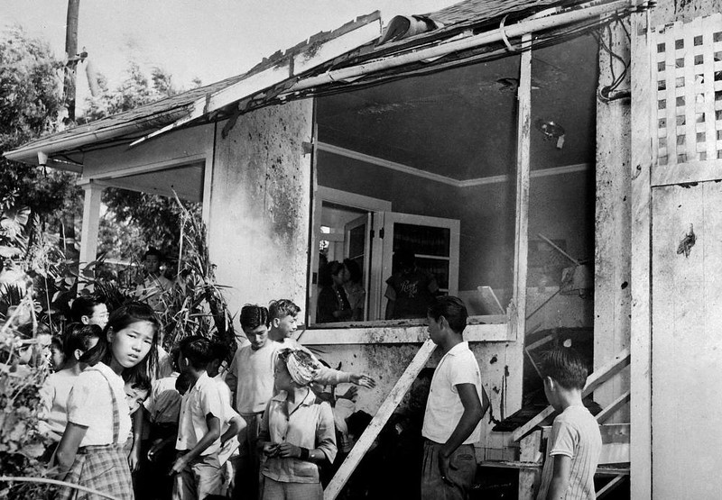 . A small crowd inspects the damage, both inside and outside, after a Japanese bomb hit the residence of Paul Goo during the raid on Honolulu Dec. 7, 1941. (AP Photo)