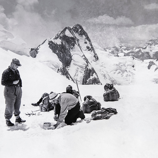 1955 Fr Doherty, John McWilliams (on stove), Bill Toomey and JER Mathews (photographer) at lunch on Tasman Saddle 1 (LF trans) a.jpg