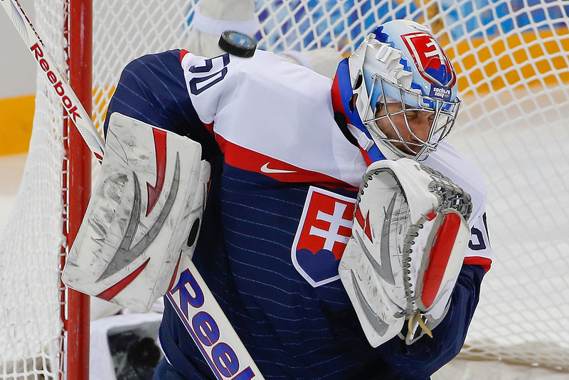 . A shot on goal flies by Slovakia goaltender Jan Laco during the first period of the 2014 Winter Olympics men\'s ice hockey game against the Czech Republic at Shayba Arena, Tuesday, Feb. 18, 2014, in Sochi, Russia. (AP Photo/Petr David Josek)