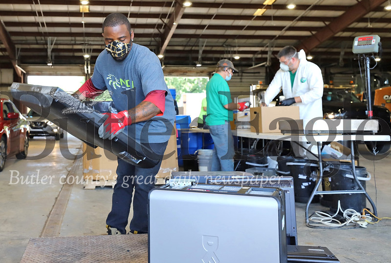 Albert Thigpen, a volunteer with ECS & R, places a flatscreen television on a scale with other electronics to be recycled saturday at Cranberry Township's electronic waste collection. Seb Foltz/Butler Eagle 06/25/20