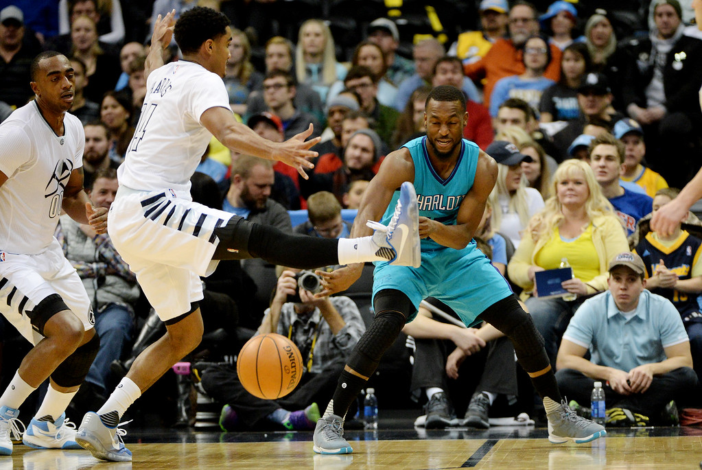 . Kemba Walker (15) of the Charlotte Hornets passes the ball past the out-stretched leg of Gary Harris (14) of the Denver Nuggets during the first quarter. The Denver Nuggets hosted the Charlotte Hornets at the Pepsi Center on Sunday, January 10, 2016. (Photo by AAron Ontiveroz/The Denver Post)