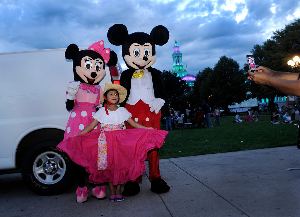 . Aly Soto, age 7, center, posed for a photo with Mickey and Minnie Mouse Thursday night as her mother Ana snapped away with a camera phone. Denver celebrated Mexico Night in Civic Center Park Thursday night, July 18, 2013. The event was part of the Biennial of the Americas which is billed as an international festival of ideas, art, and culture. Soto performs with the Colorado Mestizo Dancers. Photo By Karl Gehring/The Denver Post
