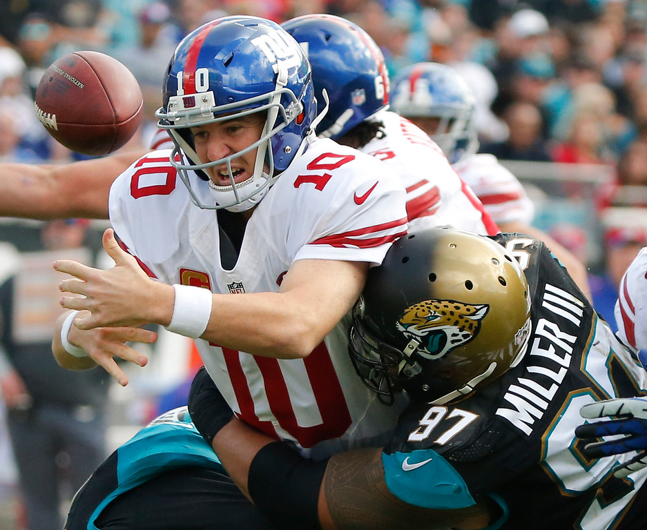 . New York Giants quarterback Eli Manning (10) fumbles the ball as he is hit by Jacksonville Jaguars defensive tackle Roy Miller (97) during the second half of an NFL football game in Jacksonville, Fla., Sunday, Nov. 30, 2014. The ball bounced in the end zone and was recovered by Jacksonville for a touchdown. (AP Photo/Stephen B. Morton)