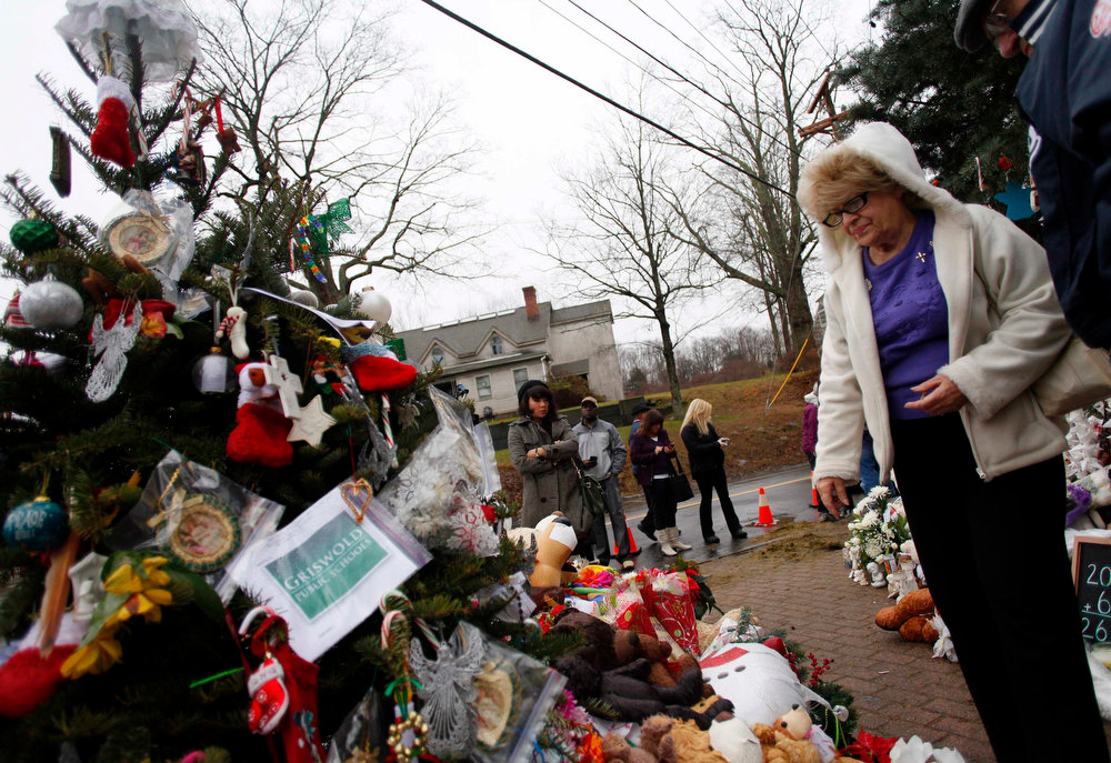Description of . A woman looks at a memorial for the victims of Sandy Hook Elementary School shooting in Newtown, Connecticut December 18, 2012. U.S. Authorities continue to investigate the December 14 massacre in Connecticut in which a heavily armed gunman entered Sandy Hook Elementary school and shot and killed 20 children and six adults. The incident, resulting in 28 deaths, including the gunman and his mother, has prompted a fresh debate on U.S. gun control. REUTERS/Joshua Lott