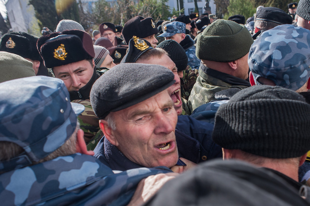 . Members of a Pro-Russian self-defense force scuffle as they try to get into the Ukrainian Navy headquarters in Sevastopol, Crimea, Wednesday, March 19, 2014.  (AP Photo/Andrew Lubimov)