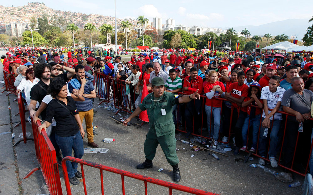 . A trooper directs people lining up to view the body of Venezuela\'s late President Hugo Chavez lying in state at the military academy in Caracas, Thursday, March 7, 2013. Battling an unspecified cancer, Chavez died Tuesday. His body was taken to the military academy Wednesday, where he started his army career, his flag-draped coffin lying in state as a mile-long line of mourners came to pay homage Thursday. (AP Photo/Ariana Cubillos)