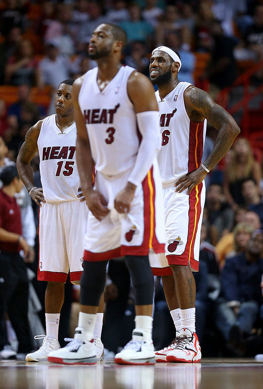 . MIAMI, FL - MARCH 14: LeBron James #6, Dwyane Wade #3 and Mario Chalmers #15 of the Miami Heat look on during a game against the Denver Nuggets at American Airlines Arena on March 14, 2014 in Miami, Florida. (Photo by Mike Ehrmann/Getty Images)