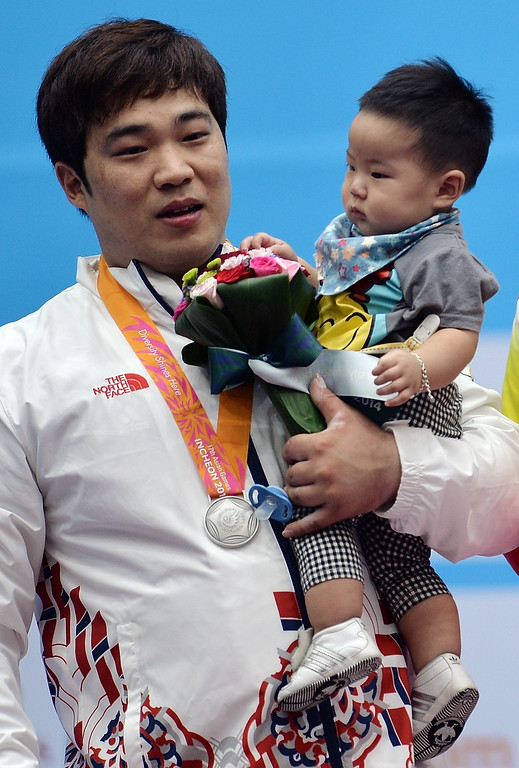 . South Korea\'s Kim Min-jae poses with his eight-month old son Kim Myung-Jun on the podium after the mens 105 kg weightlifting final of the 2014 Asian Games at the Moonlight Festival Garden weightlifting venue in Incheon on September 26, 2014.  MANAN VATSYAYANA/AFP/Getty Images
