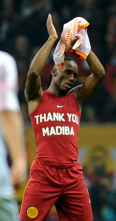 """. Galatasaray`s Didier Drogba from Ivory Coast wears a t-shirt with text reading \""""Thank you Madiba\"""" in honor of late former South African President Nelson Mandela, during a Turkish super league match between Galatasaray and Elazigspor match on December 6, 2013, at Turk Telekom Arena, in Istanbul. People gathered in cities around the world to make their own personal tributes to Nelson Mandela on December 6, leaving flowers and setting up makeshift shrines in an outpouring of emotion for South Africa\'s anti-apartheid icon. AFP PHOTO/STRSTR/AFP/Getty Images"""