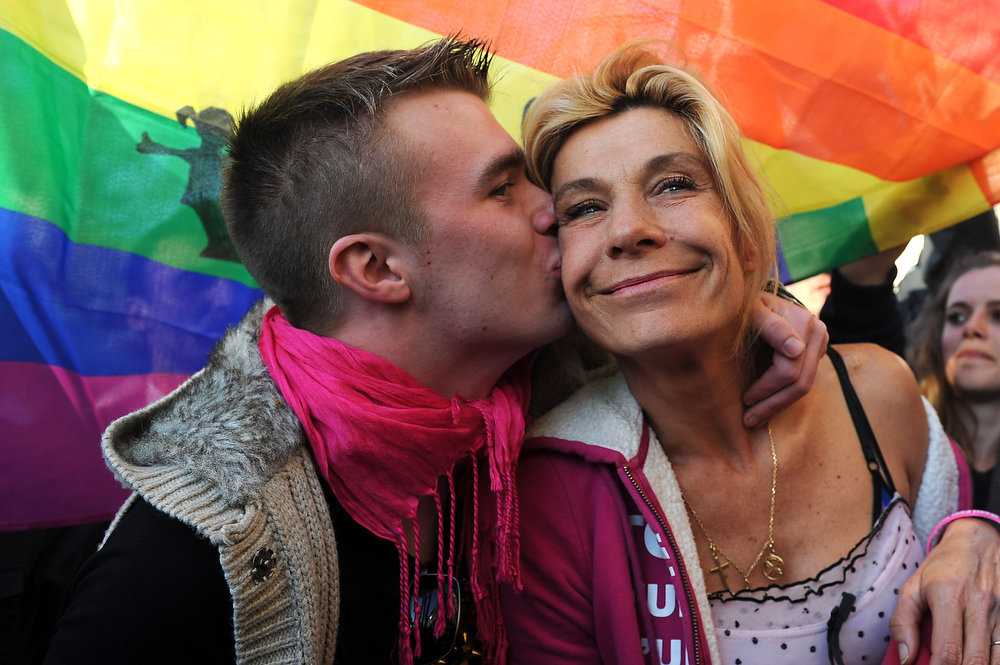 . A supporter kisses anti-same sex marriage activist Frigide Barjot (C) of the anti-gay marriage movement \'la Manif pour Tous\' during a demonstration, a few hours after the French Parliament adopted gay marriage law at the Assemblee Nationale on April 23, 2013 in Paris, France. The bill was approved by a vote in Parliament of 331 to 225. (Photo by Antoine Antoniol/Getty Images)