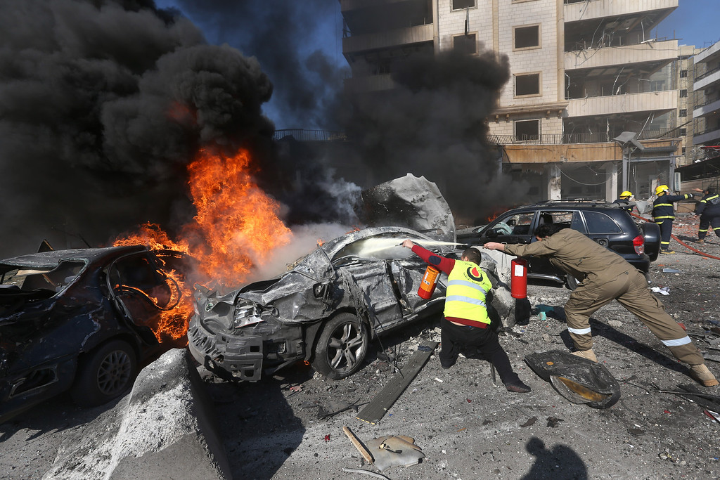 . Lebanese firefighters extinguish burned cars at the site of an explosion, near the Kuwaiti Embassy and Iran\'s cultural center, in the suburb of Beir Hassan, Beirut, Lebanon, Wednesday, Feb. 19, 2014. (AP Photo/Hussein Malla)